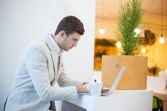 Homme à l'aide de l'ordinateur portable dans le bureau Image libre de droits