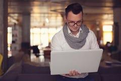 Homme à l'aide de l'ordinateur portable dans le bureau de démarrage Image libre de droits