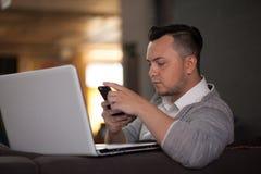 Homme à l'aide de l'ordinateur portable et du téléphone dans le bureau Photos stock