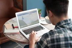 Homme à l'aide de l'ordinateur portable, identifiez-vous en compte de Facebook image stock