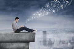 Homme à l'aide de l'ordinateur portable sur le dessus de toit Image libre de droits