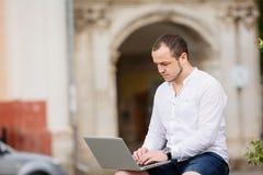 Homme à l'aide de l'ordinateur portable sur un banc dans le parc photographie stock