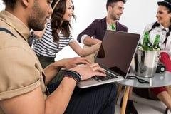 Homme à l'aide de l'ordinateur portable tandis que jeunes amis heureux buvant de la bière Photos libres de droits