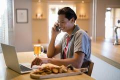 Homme à l'aide de l'ordinateur portable tout en parlant au téléphone portable dans un restaurant Photo stock