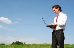 Homme à l'aide de l'ordinateur portatif à l'extérieur Image libre de droits