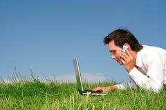 Homme à l'aide de l'ordinateur portatif à l'extérieur image stock