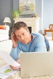 Homme à l'aide de l'ordinateur portatif pour manager des factures s'étendant sur la couverture Photos libres de droits