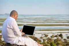 Homme à l'aide de l'ordinateur portatif tout en ayant ses vacances Photographie stock