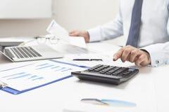 Homme à l'aide de la calculatrice et tenant le document important Photo stock