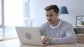 Homme à l'aide de l'ordinateur portable au travail photo libre de droits