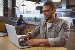 Homme à l'aide de l'ordinateur portable avec l'ami à l'arrière-plan au café Images stock