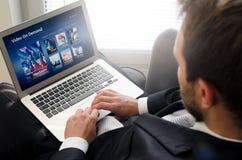 Homme à l'aide de l'ordinateur portable pour le film de observation au service de VOD image stock