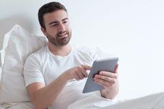 Homme à l'aide de son comprimé électronique se trouvant dans le lit Photos libres de droits