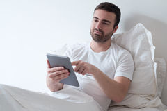 Homme à l'aide de son comprimé électronique se trouvant dans le lit Photo stock