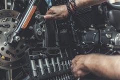 Homme à l'aide des outils pour la motocyclette de réparation Photo stock