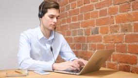 Homme à l'aide du casque pour parler, travaillant en ligne photos stock