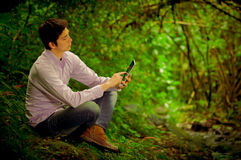 Homme à l'aide du comprimé dans la forêt Photo libre de droits