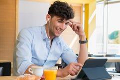 Homme à l'aide du comprimé numérique au café Photos stock