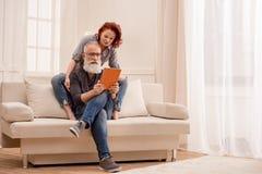 Homme à l'aide du comprimé numérique avec l'épouse tout près à la maison Images stock