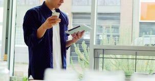 Homme à l'aide du comprimé numérique et du téléphone portable clips vidéos