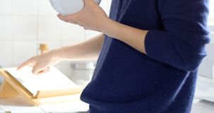 Homme à l'aide du comprimé numérique tout en ayant le bol de céréale de petit déjeuner 4k clips vidéos