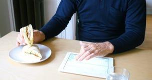 Homme à l'aide du comprimé numérique tout en prenant le petit déjeuner dans le salon 4k banque de vidéos