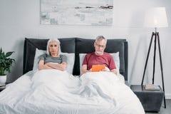 Homme à l'aide du comprimé tandis qu'épouse grincheuse se trouvant dans le lit photographie stock