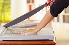 Homme à l'aide du coupeur de papier manuel pour couper les factures imprimées dans les feuilles de papier, sur une table en bois, photos stock