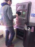 Homme à l'aide du distributeur automatique inverse photographie stock