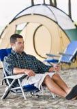 Homme à l'aide du joueur mp3 au terrain de camping Photos stock