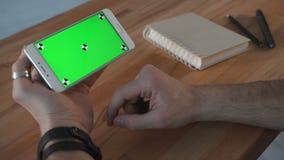 Homme à l'aide du smartphone avec l'écran vert à la table clips vidéos
