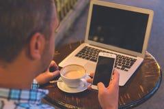 Homme à l'aide du smartphone et de l'ordinateur portable tout en appréciant le café à l'étiquette Image libre de droits