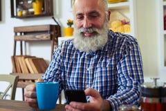 Homme à l'aide du smartphone et tenant une tasse de thé à la maison Image libre de droits