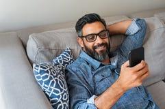Homme à l'aide du smartphone à la maison photographie stock libre de droits