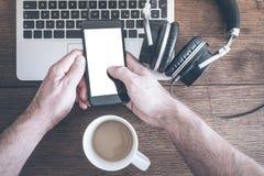Homme à l'aide du smartphone sur la table en bois avec l'ordinateur portable, les écouteurs et la tasse de café images libres de droits