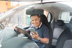 Homme à l'aide du smartphone tout en conduisant une voiture photos libres de droits