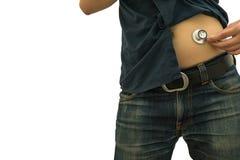 Homme à l'aide du STÉTHOSCOPE sur le fond de blanc d'estomac photographie stock libre de droits