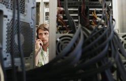 Homme à l'aide du téléphone entouré par le matériel informatique photographie stock libre de droits