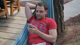 Homme à l'aide du téléphone intelligent mobile tout en détendant dans un hamac banque de vidéos
