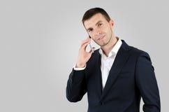 Homme à l'aide du téléphone intelligent sur le fond gris photos stock