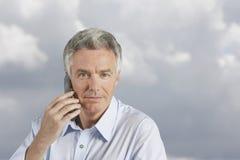 Homme à l'aide du téléphone portable en Front Of Clouds Photo stock