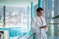 Homme à l'aide du téléphone portable près de la piscine d'intérieur photographie stock libre de droits