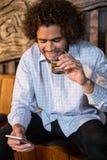 Homme à l'aide du téléphone portable tout en ayant le whiskey photo libre de droits