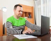 Homme  à l'ordinateur dans la maison images stock