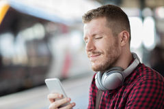 Homme à la gare ferroviaire utilisant le téléphone portable sur la plate-forme photo stock