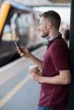 Homme à la gare ferroviaire utilisant le téléphone portable sur la plate-forme images libres de droits