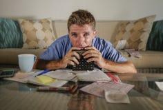 Homme à la maison inquiété et soumis à une contrainte attirant calculant des dépenses d'impôts de mois avec des paiements de comp Photographie stock libre de droits