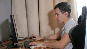 Homme à la maison mangeant une tranche de pizza et jouant sur l'ordinateur banque de vidéos