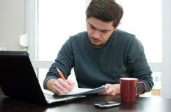 Homme à la maison travaillant sur un ordinateur portatif photo libre de droits