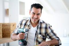 Homme à la maison utilisant les outils électriques Image libre de droits